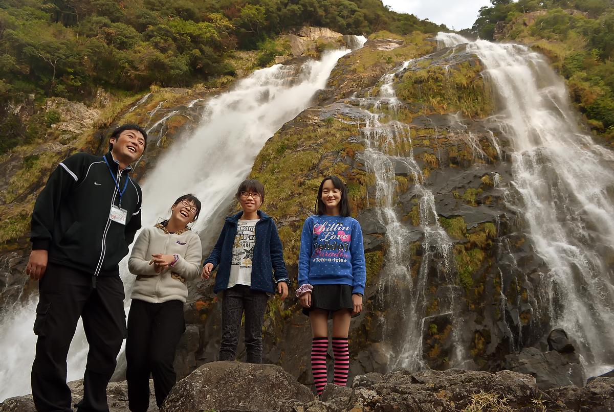 屋久島にある巨大な滝の前で、研修センターのインストラクターのお兄さんと記念撮影