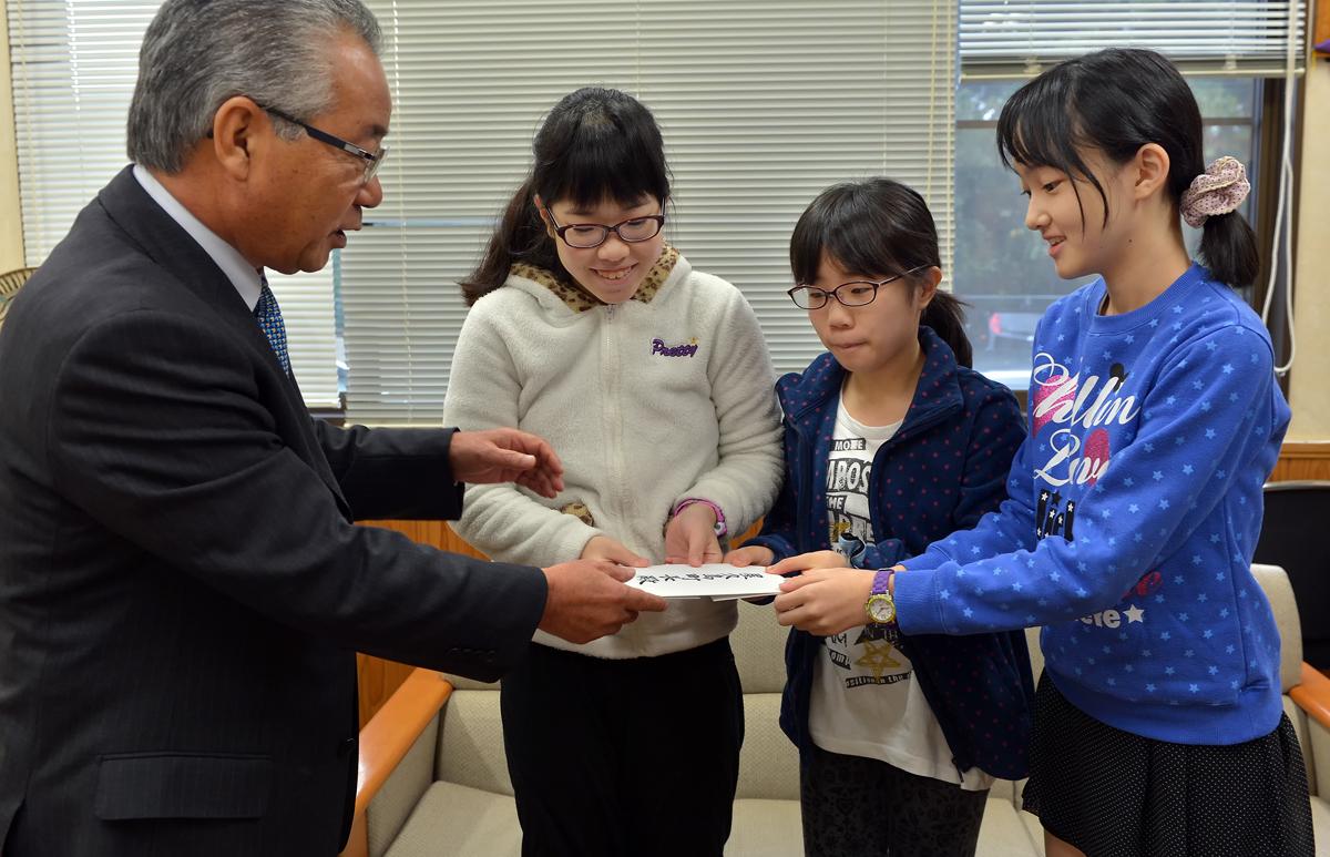 屋久島町長に深浦町の吉田町長からの親書を手渡す。大役に少し緊張気味