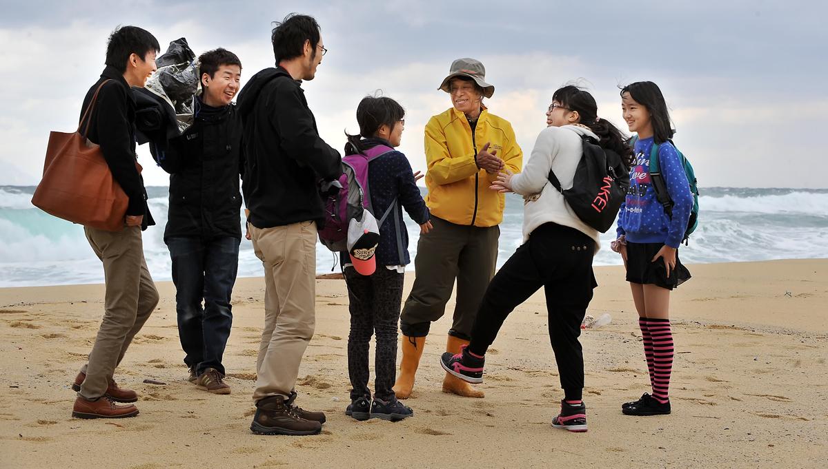 報道関係者に取り囲まれながら、ウミガメが上陸する永田浜を歩く