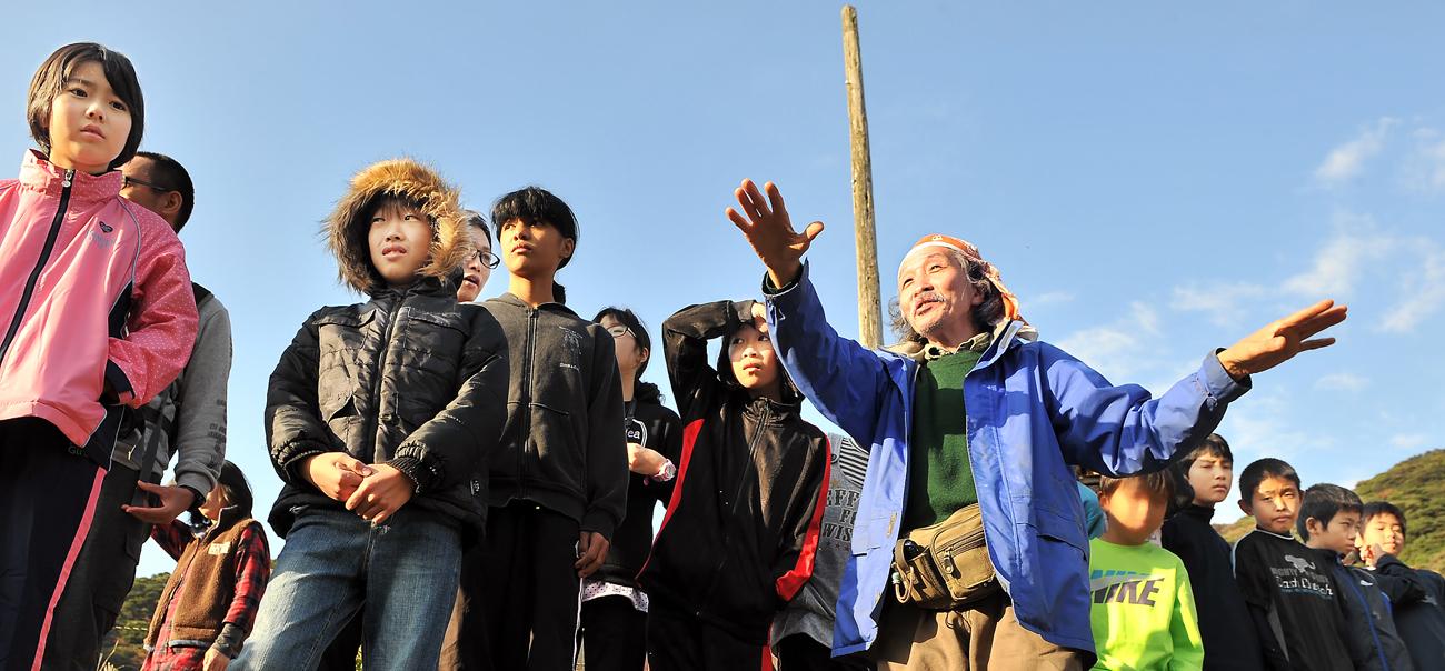 一湊川で、子供たちにヤクシマカワゴロモの説明をする手塚さん
