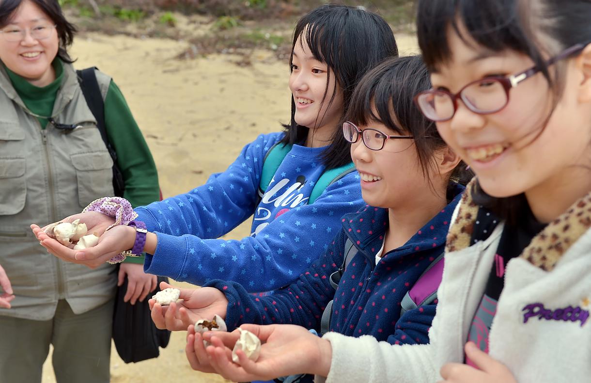 砂浜で拾ったウミガメの卵の殻をカメラマンに見せる