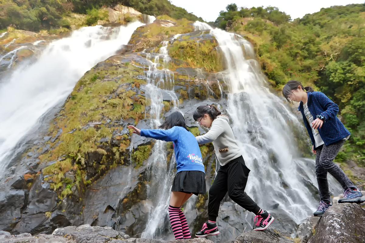 大川の滝を間近で見るため、岩の上を飛ぶ跳ねるように走る3人娘。危ないよ!