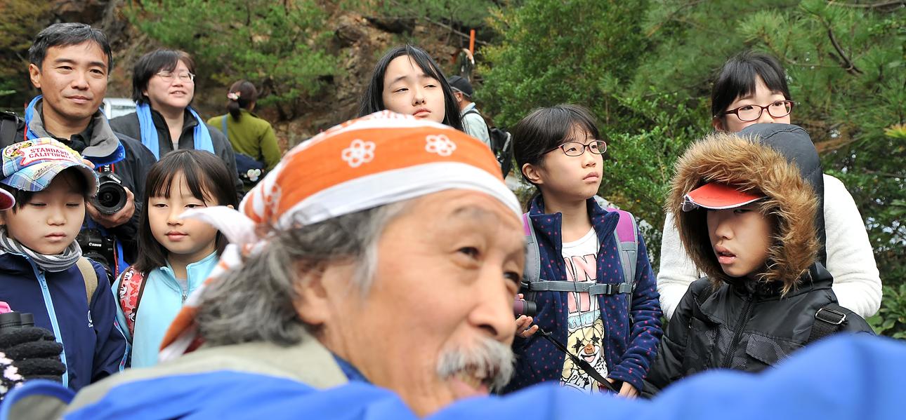 手塚さん(手前)から説明を受ける両地域の子供たち