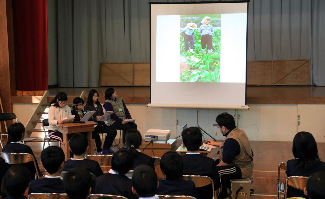 八幡小の児童たちに、写真を見せながら発表する