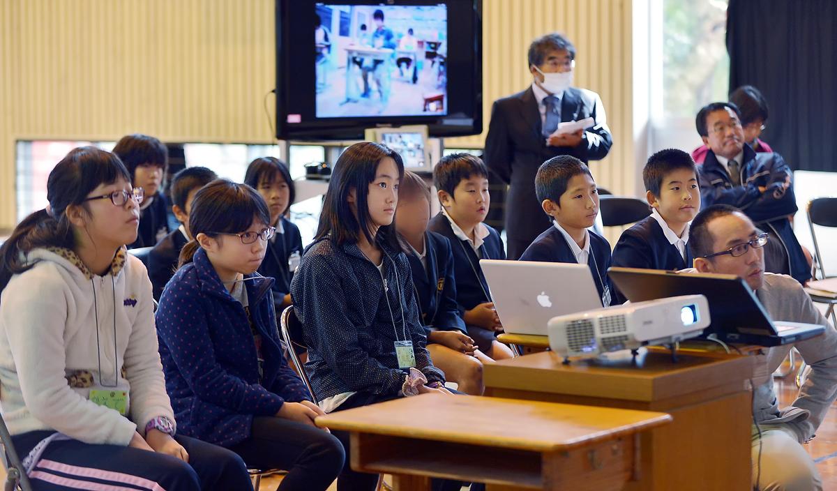 屋久島側の発表を聞く三人娘。後方のテレビ画面には、インターネット電話で繋がるいわさき小六年生の教室