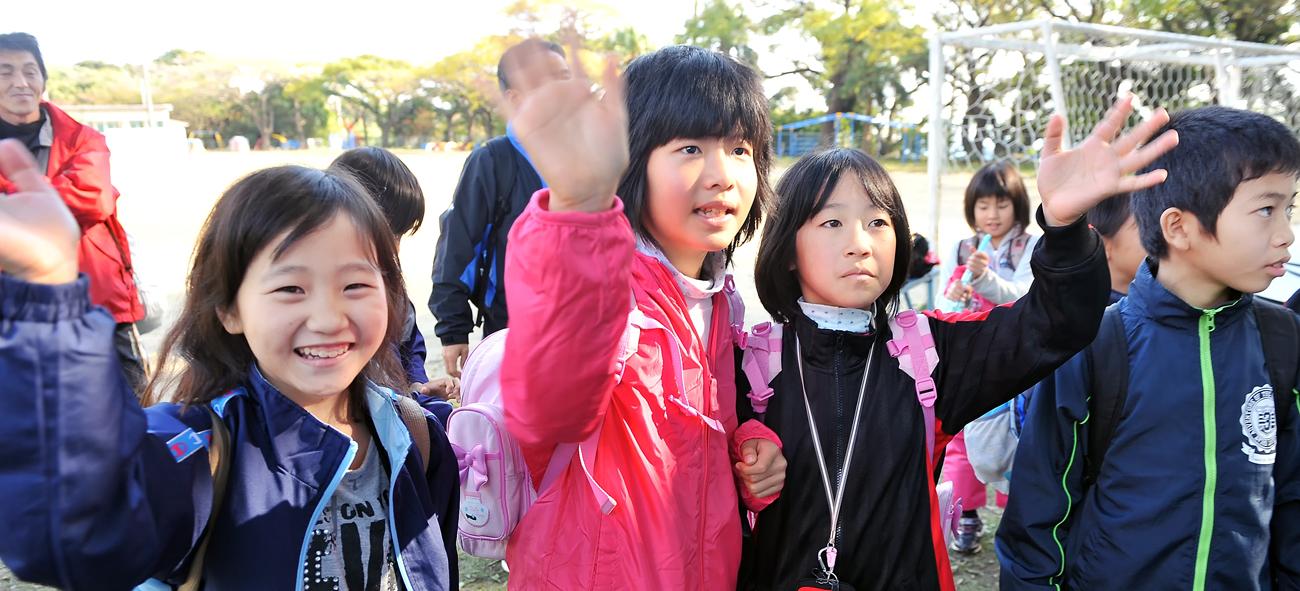 手を振って別れを惜しむ八幡小学校の児童たち
