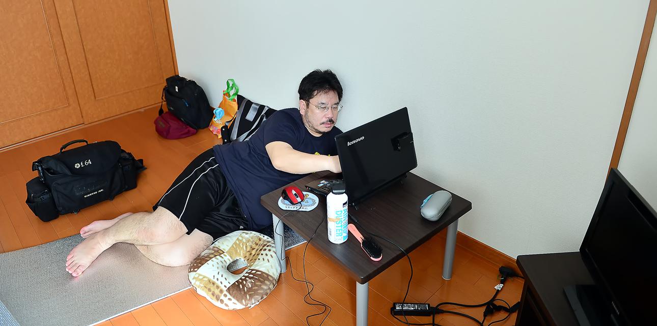 部屋でパソコンを見る筆者②。暑いからと言いながら、このスタイル。ホッチャレてきていることに気づかないようだ