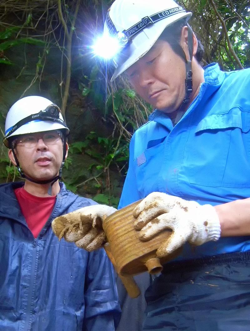 出土した防毒吸収管を手にする楠田代表(右)