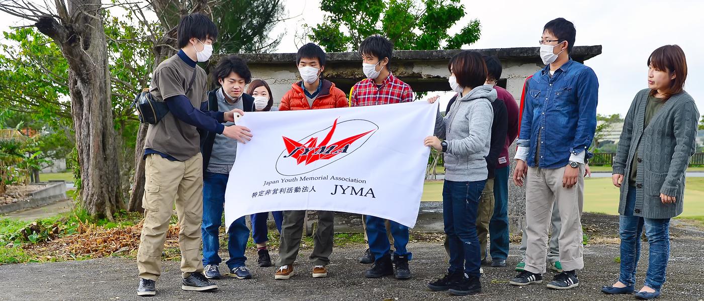 団旗を手に集まるJYMAのメンバーたち