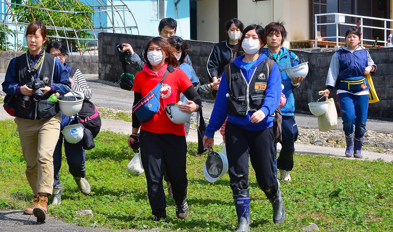 民家が並ぶ丘の上で遺骨収集の現場に向かう学生たち