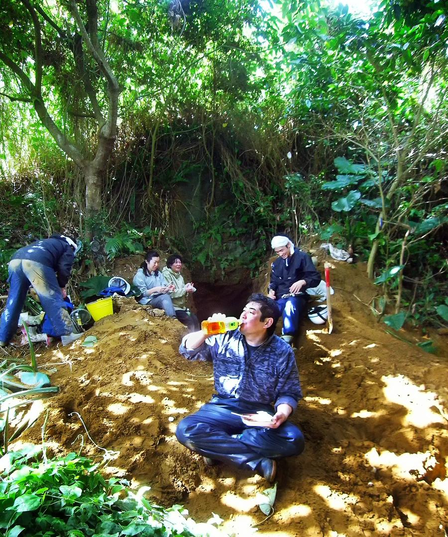壕の入り口に積み上がったニービの上で、お昼ご飯を食べる楠田代表ら会のメンバー