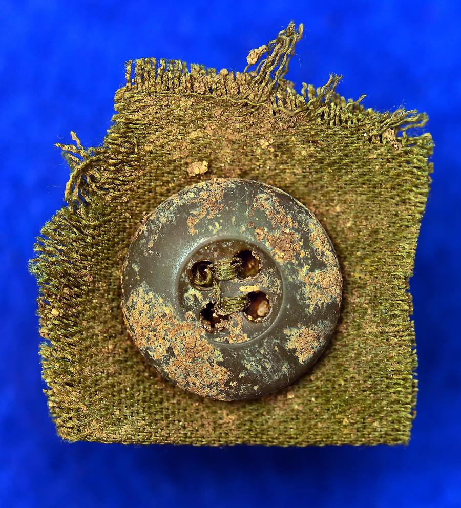 軍服の生地が着いたままのボタン。糸もきれいに残っている