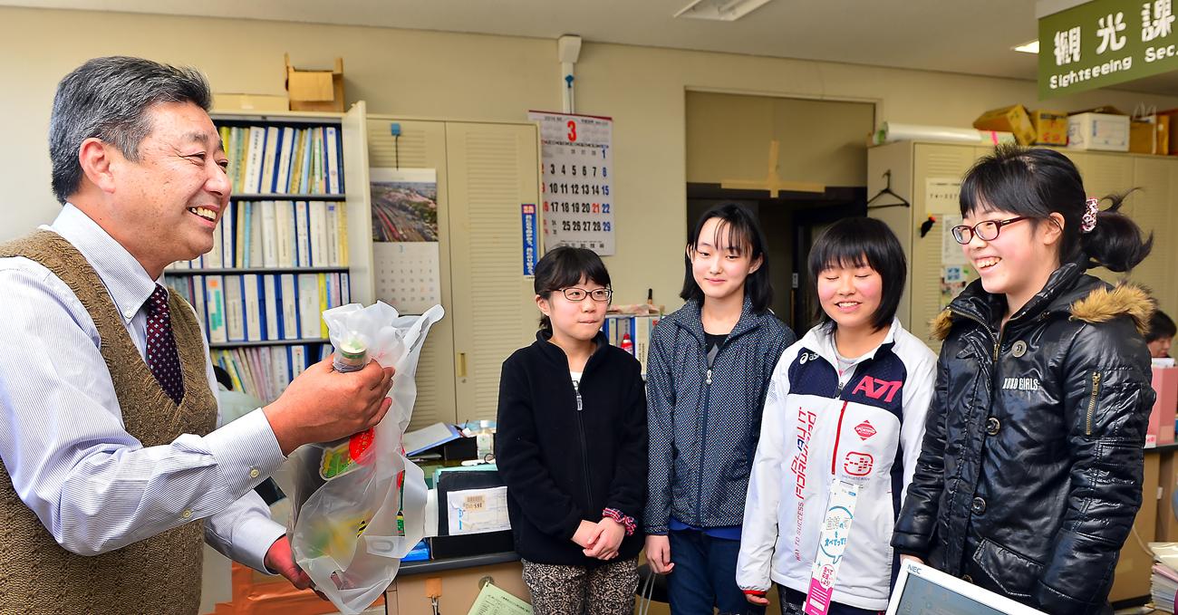 白神と屋久島のメンバーから贈られた屋久島焼酎の「三岳」を手に笑顔の七戸課長