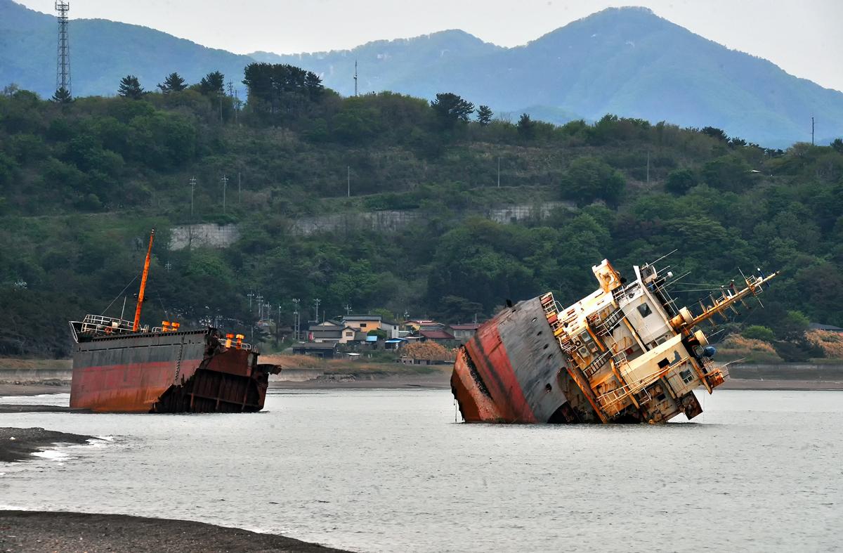 船体が真っ二つに折れてしまった座礁船。後方は森山地区の家並みと白神の山々