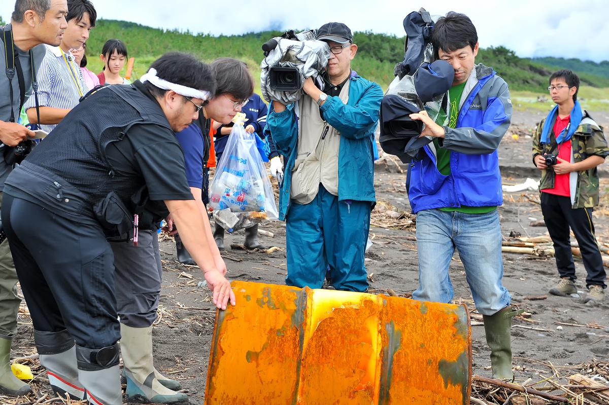 ドラムカンの説明をする場面を取材する報道関係者