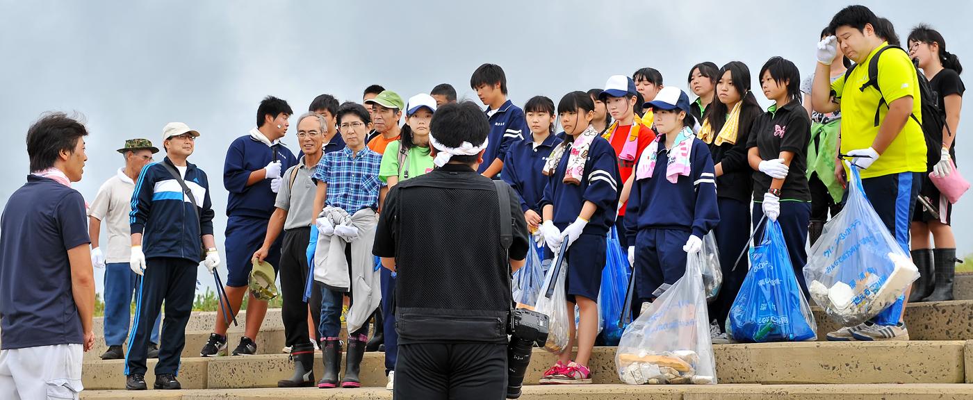 哲二(手前)と町役場の松沢戦略室・室長の話を聞く参加者