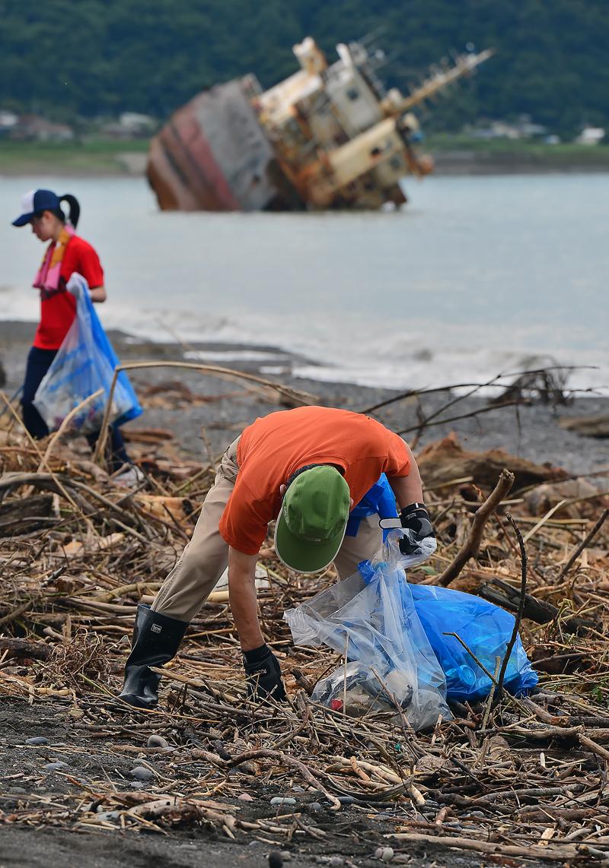 放置されたままのアンファン号と海岸清掃をする町民