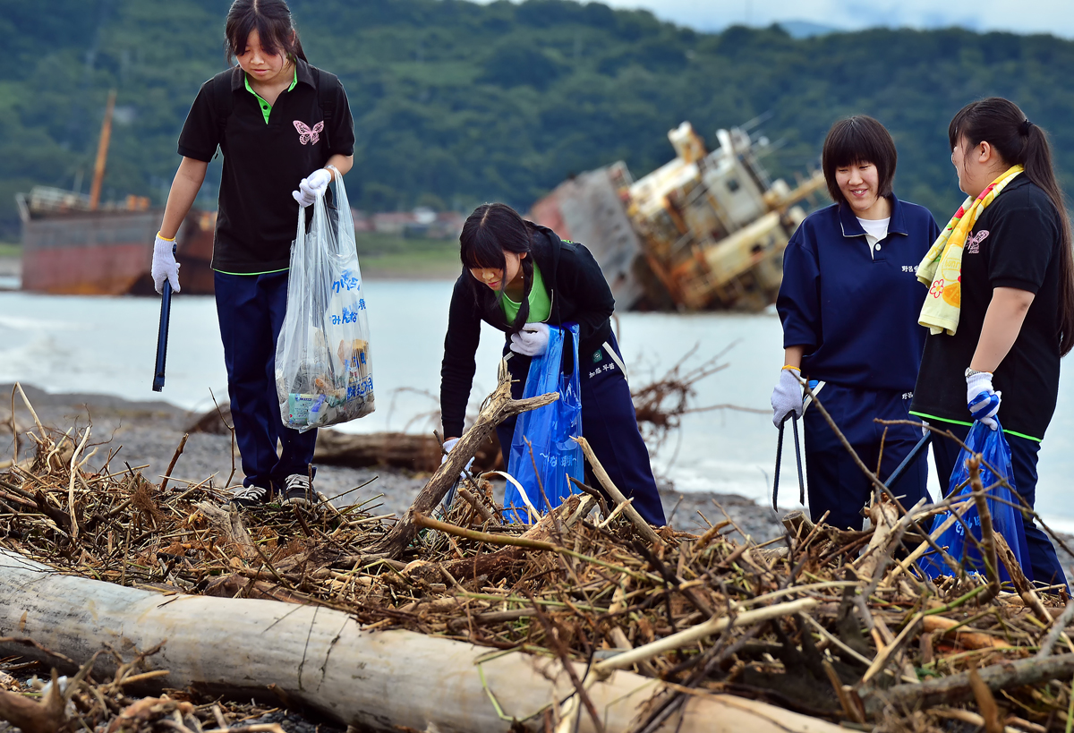 ゴミの山を乗り越えて収集活動する女子生徒たち