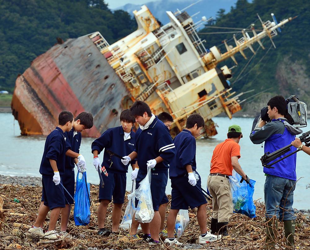 折れて傾いた船体の横でゴミを拾う生徒たち