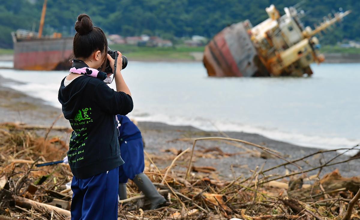 海岸で、カメラを構える香純さん。同窓生の表情を見事に捉えていた