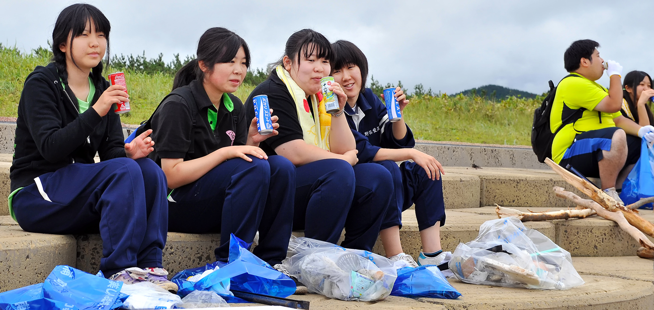 台風の接近で、曇天だが蒸暑い。スポーツドリンクで水分補給する女子生徒たち