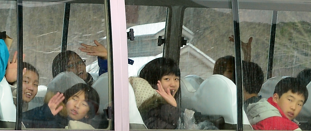 バスの中から手を振る屋久島の子どもたち