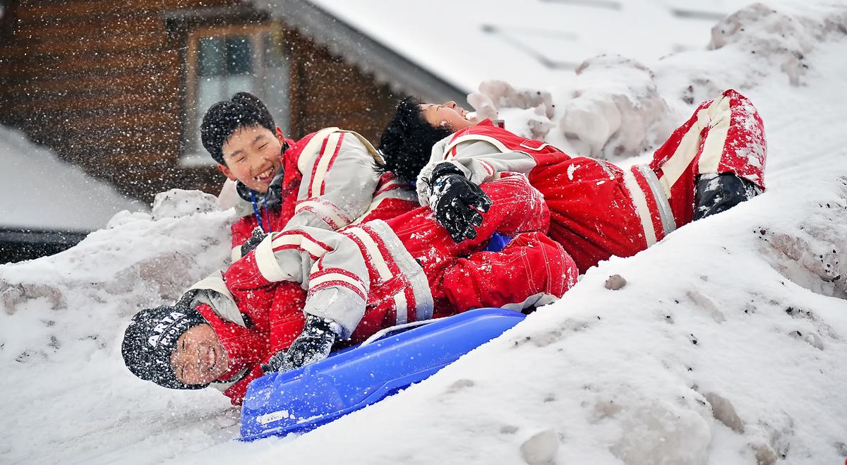 雪の滑り台でソリ遊び。笑顔がはじける