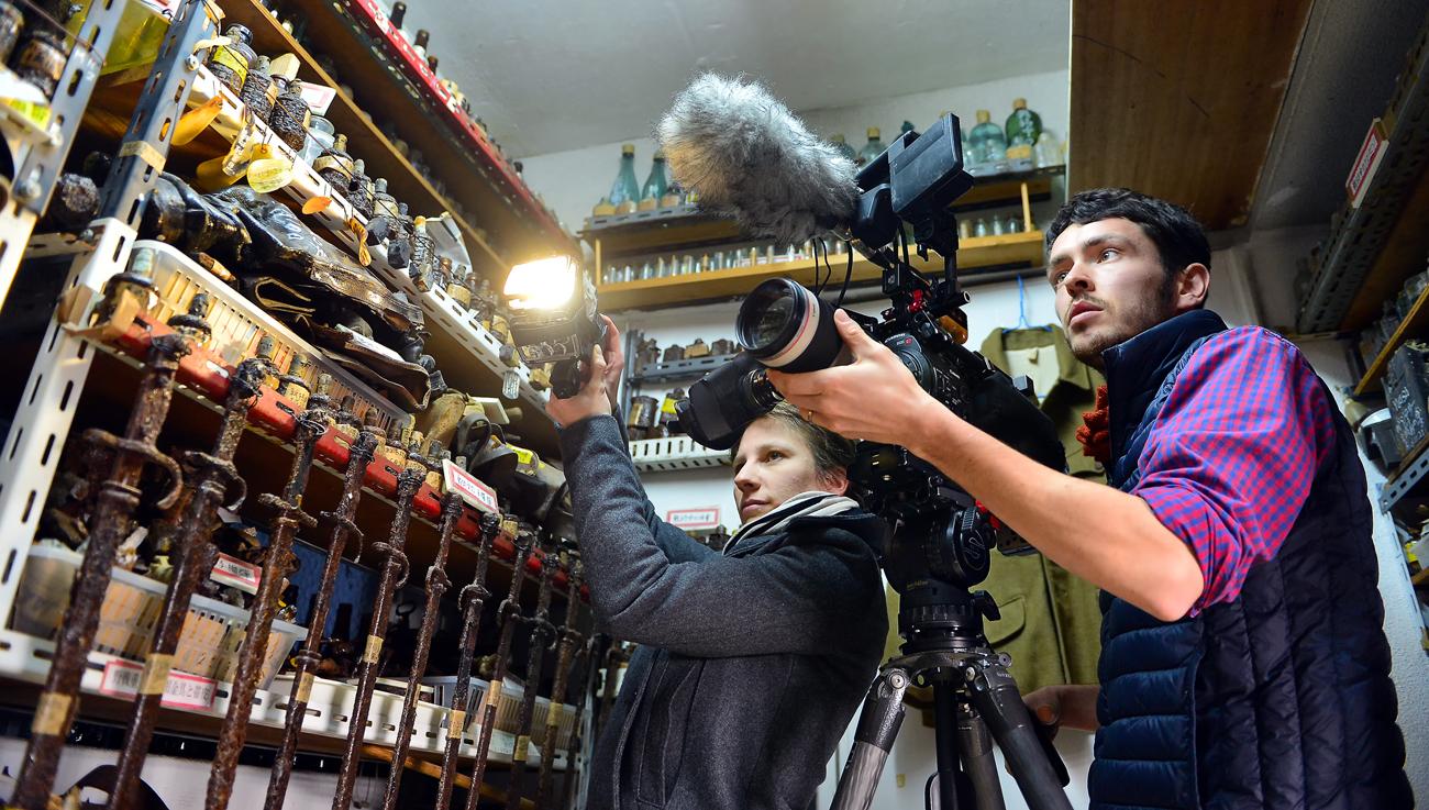 国吉さんの戦争資料館でカメラを構えるQさん(右)とMさん