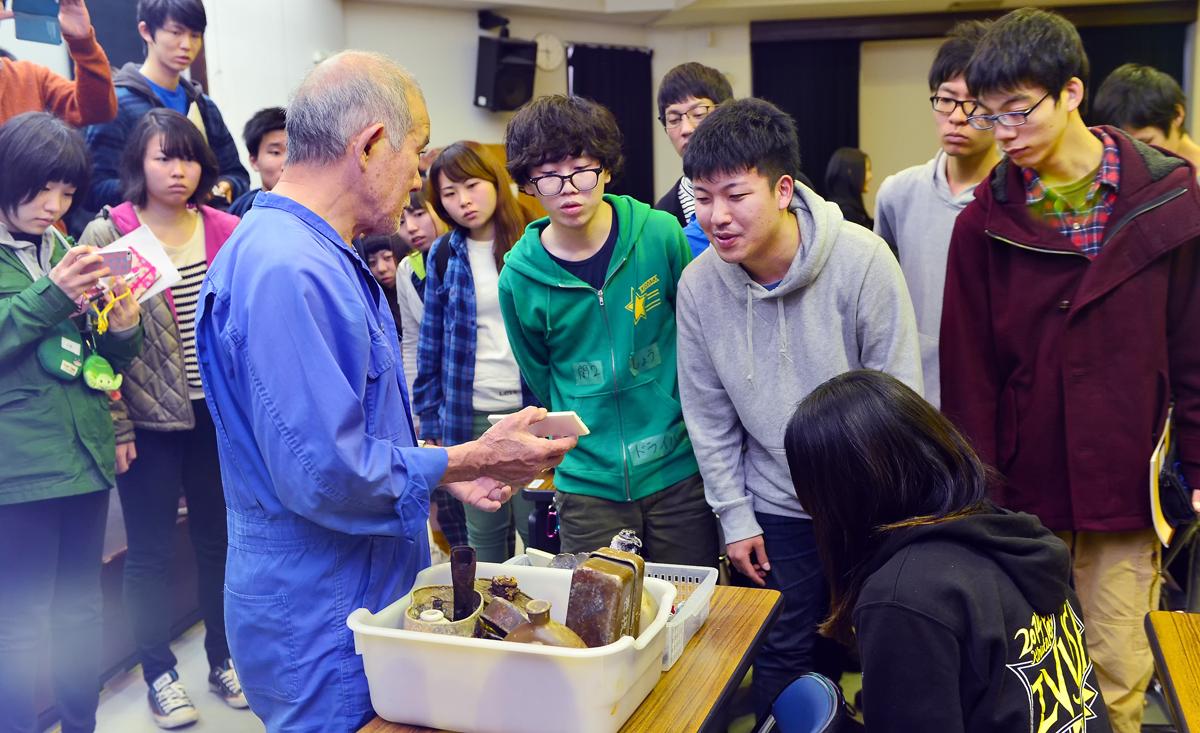 学生たちに戦没者の遺留品を見せる国吉勇さん