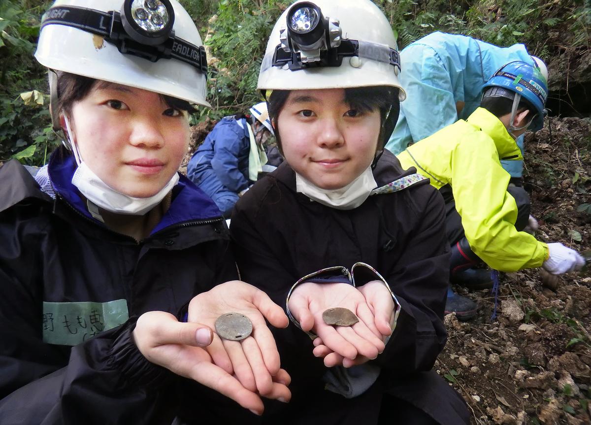 掘り出した旧日本軍の認識票を見せる女子学生