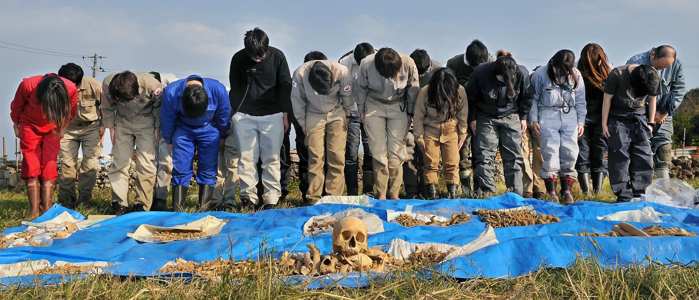 掘り出した遺骨に拝礼するJYMAの学生たち