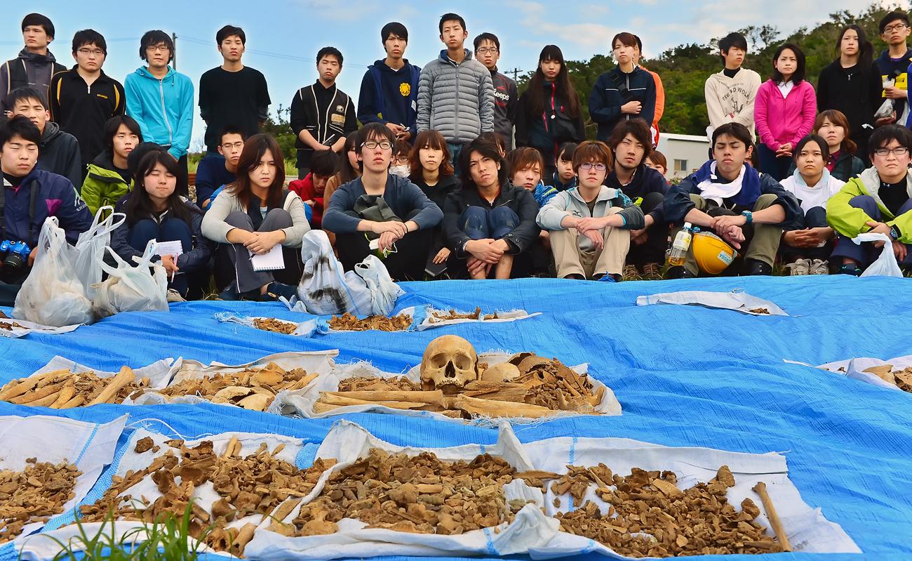掘り出した遺骨を前に、納骨する手順などの説明を聞く学生たち
