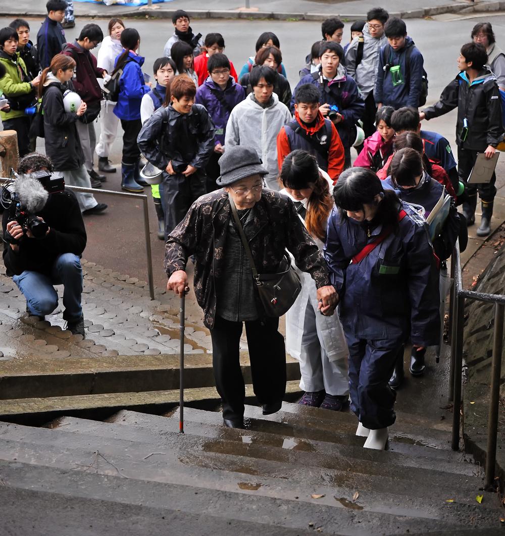 学生に付き添われて階段を登るきくさんを撮影