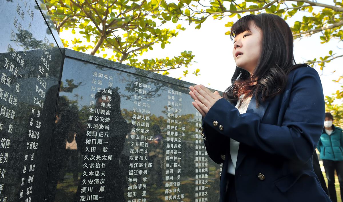 礎に刻まれた戦没者に、鳴きながら手を和え焦る女子学生
