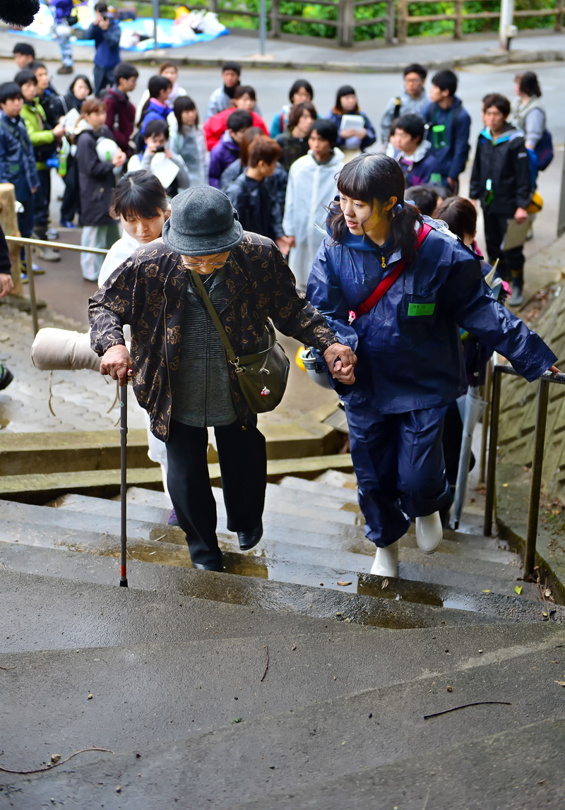 学生の手を借りて急な階段を一歩ずつ登るきくさん