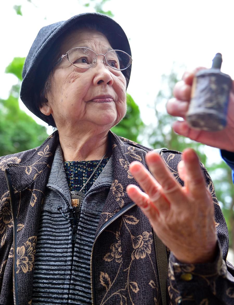 国吉勇さんが所有する旧日本軍の手榴弾を手にするきくさん