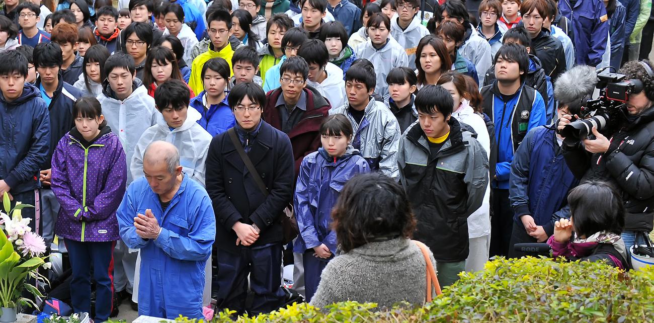 白梅の搭に祈る国吉さんや学生たちを撮影する