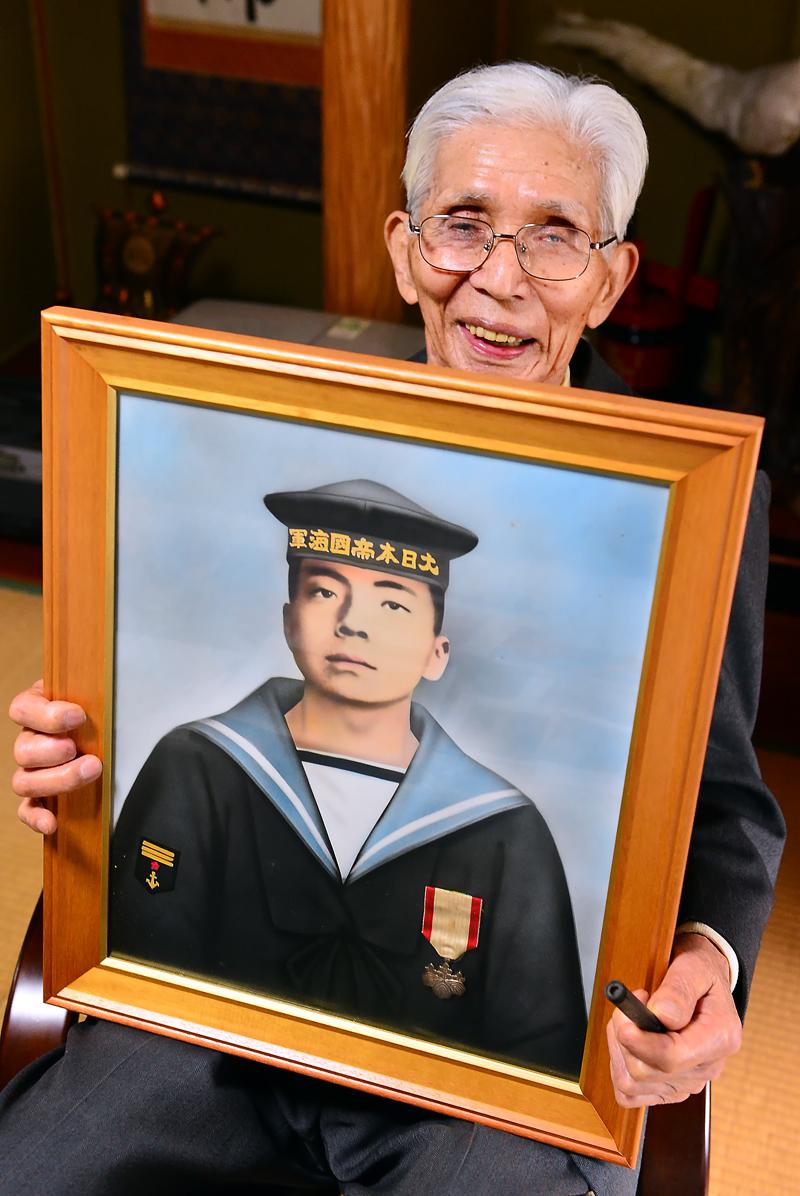 隼人さんの肖像画を手に笑顔を見せる篤さん