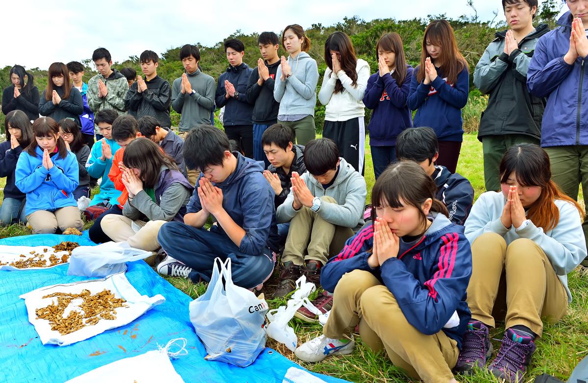 収容した遺骨に祈る学生たち