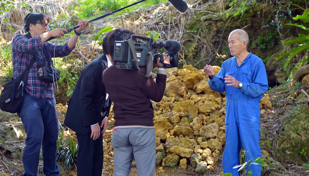 発見場所の前でNHKの取材チームに説明する国吉勇さん