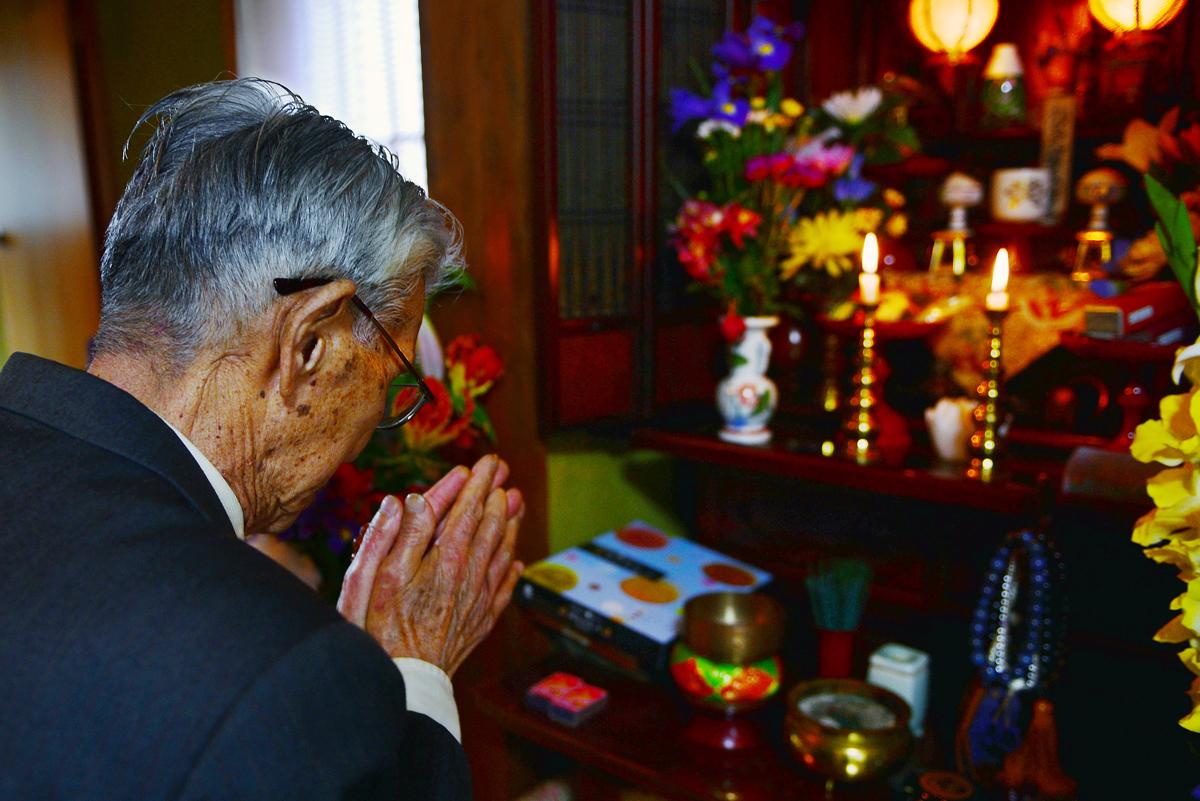 万年筆を仏壇に供え、手を合わせる篤さん