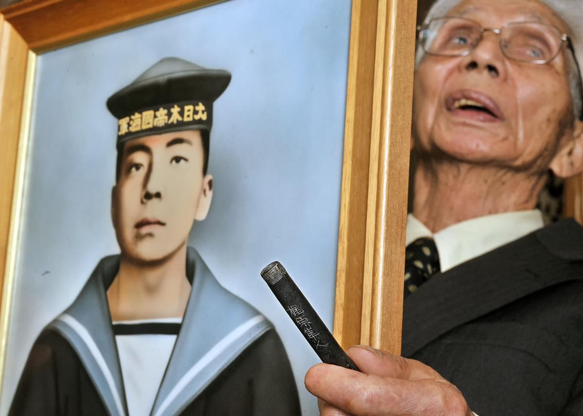 兄隼人さんの肖像画を手に笑顔を見せる篤さん