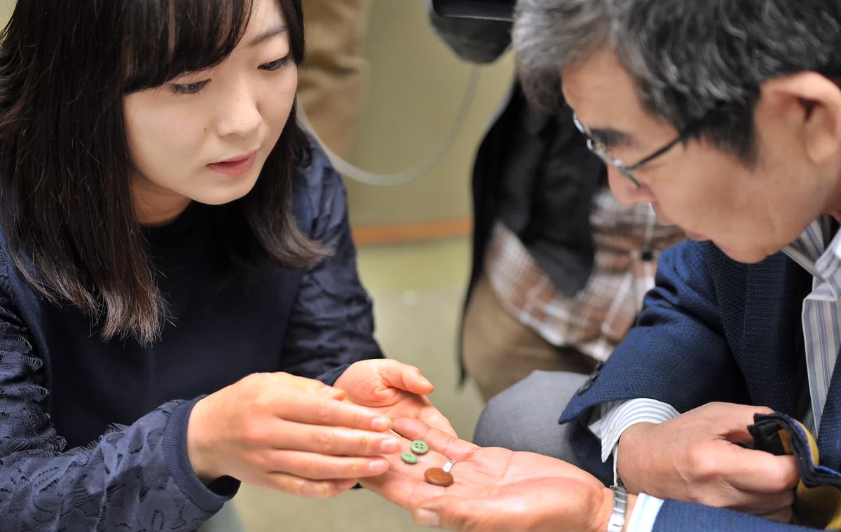 信之さんにボタンを手渡すIVUSAの新井裕香さん