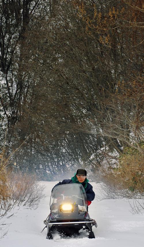 冬場の狩猟で、スノーモービルに乗る親方