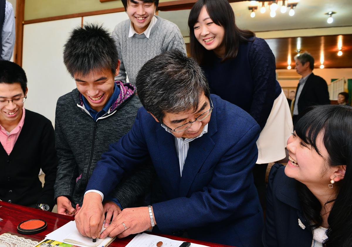 学生から、遺留品の印鑑などを受け取った灰原信之さん(中央)