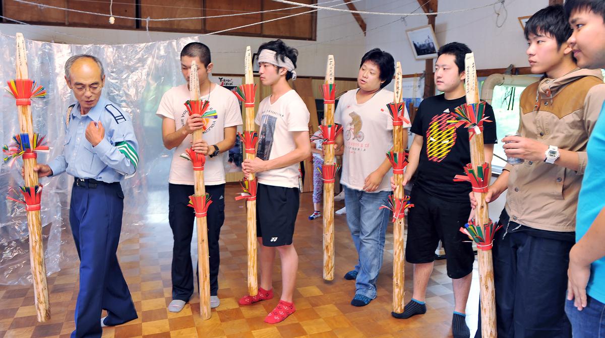 柴田さんから踊りの手順を習う6人の男子学生