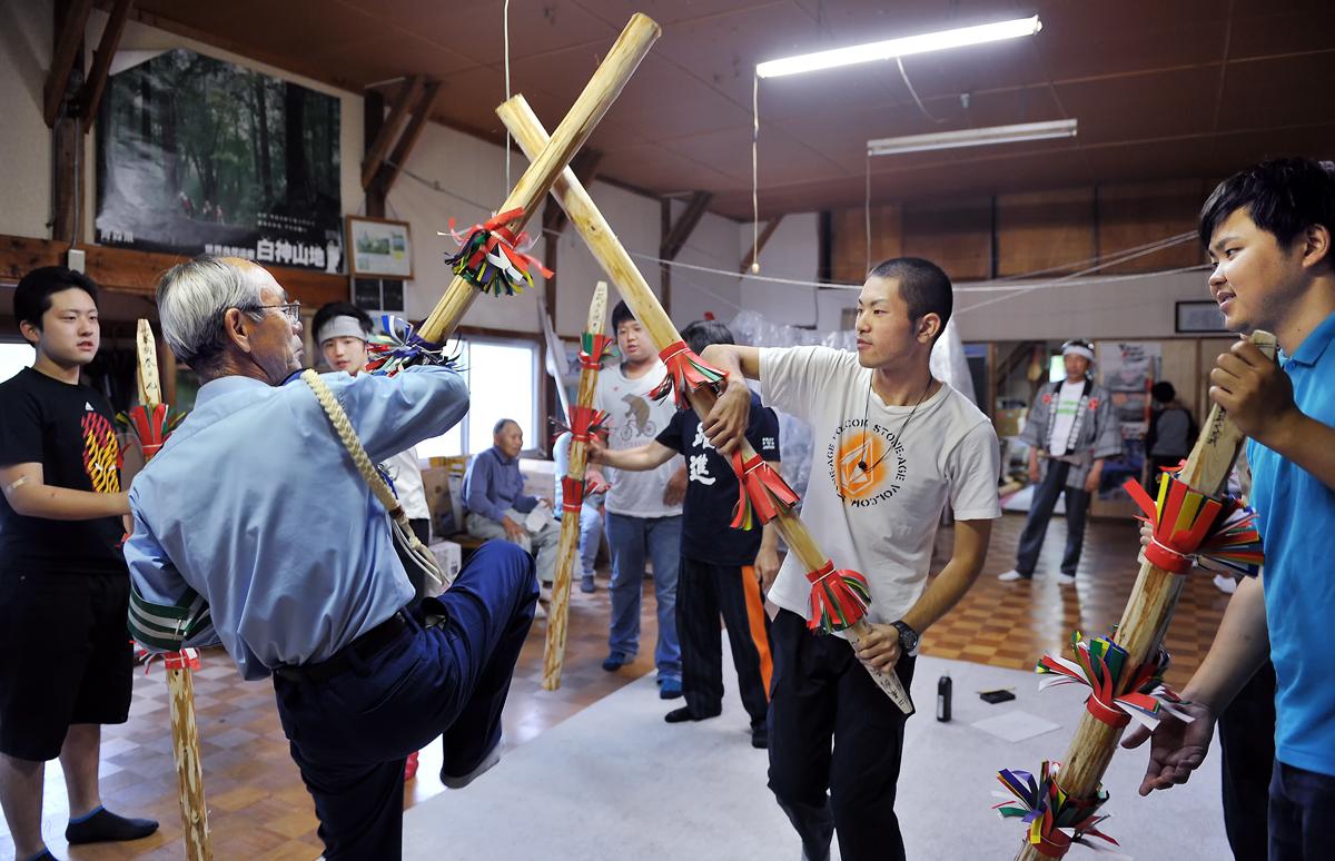 神事が始まる前、保存会の柴田さん(左)から踊り方を習う学生たち
