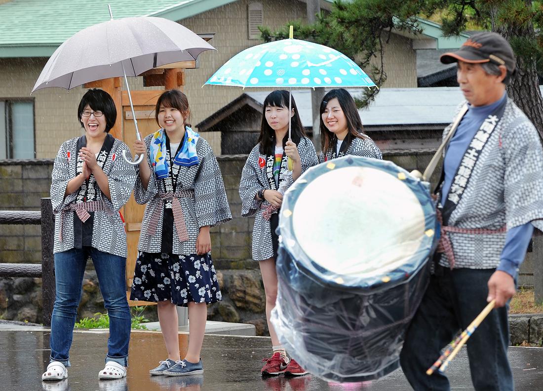 雨の中、傘を差しながら、見守る女子学生たち