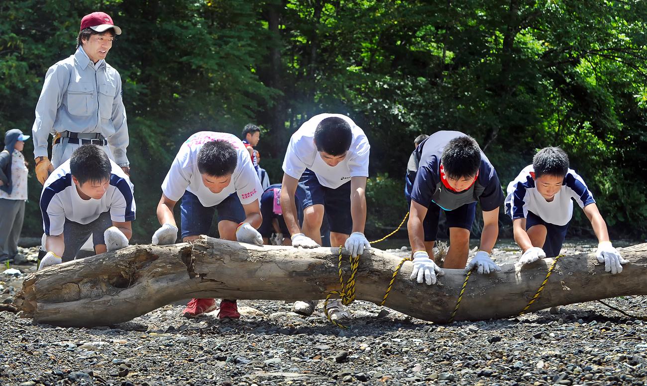 力持ちの男子たちが巨大な流木を転がして移動させる