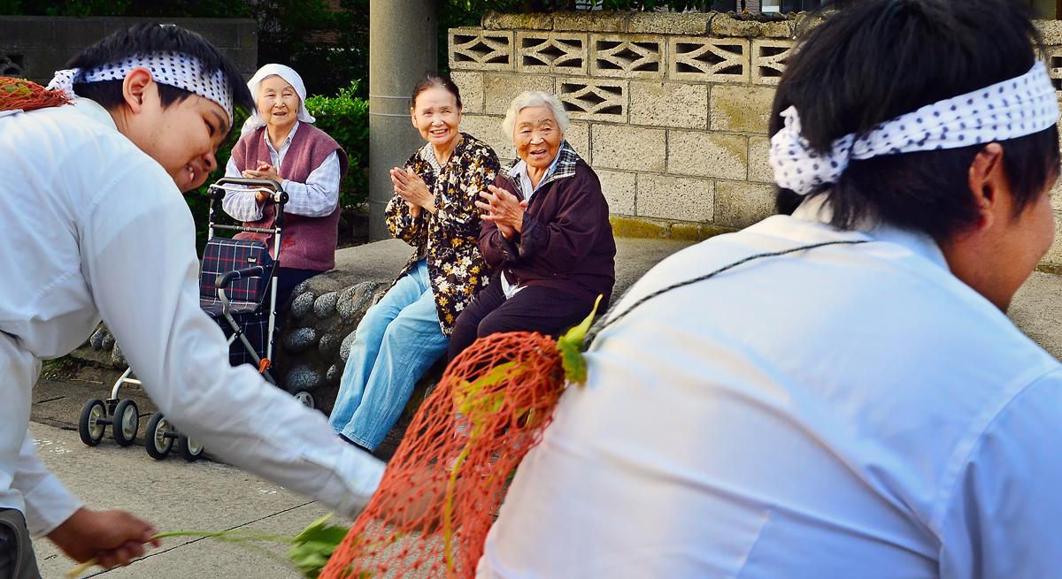 祭囃子に手拍子を取りながら、笑顔で踊りを見るお年寄りたち